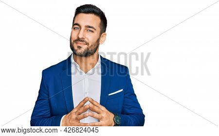 Young hispanic man wearing business jacket hands together and fingers crossed smiling relaxed and cheerful. success and optimistic
