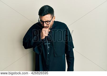 Young hispanic man wearing priest uniform standing over white background feeling unwell and coughing as symptom for cold or bronchitis. health care concept.