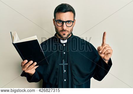Young hispanic priest man holding bible with finger up skeptic and nervous, frowning upset because of problem. negative person.