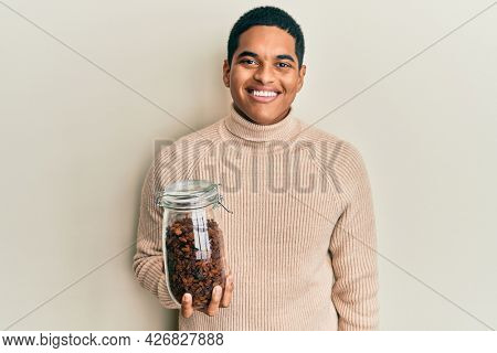 Young handsome hispanic man holding jar full of raisins looking positive and happy standing and smiling with a confident smile showing teeth