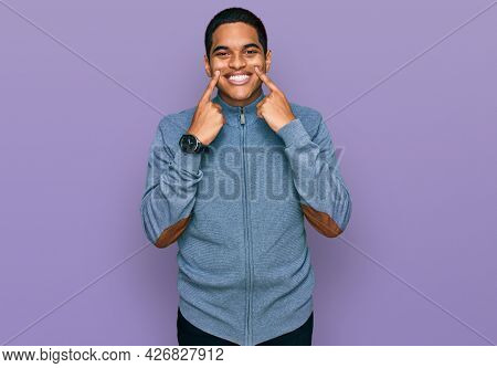 Young handsome hispanic man wearing casual sweatshirt smiling with open mouth, fingers pointing and forcing cheerful smile