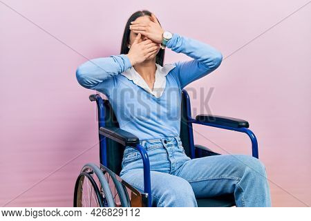Beautiful woman with blue eyes sitting on wheelchair covering eyes and mouth with hands, surprised and shocked. hiding emotion