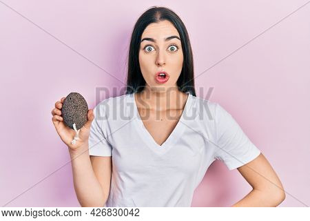 Beautiful woman with blue eyes holding pumice stone scared and amazed with open mouth for surprise, disbelief face