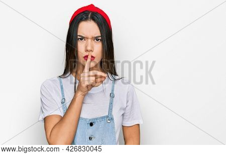 Young hispanic girl wearing casual clothes asking to be quiet with finger on lips. silence and secret concept.