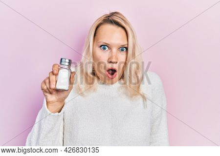 Beautiful caucasian blonde woman holding salt scared and amazed with open mouth for surprise, disbelief face