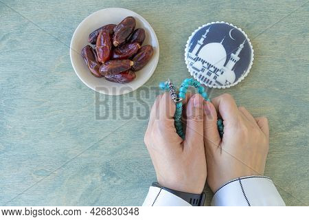 Concept Of Muslim.top View Of Female Hands Holding Rosary Near Dates And Gingerbread With Mosque. Mu