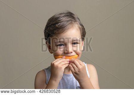 Little Child Eating Fruit. Handsome And Happy Boy Eating Ripe, Sweet, Juicy, Fresh Orange. Concept O