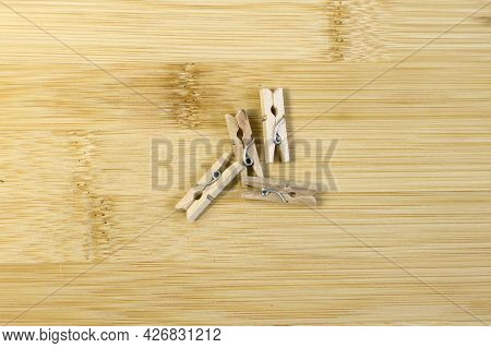 Wooden Clothespins On Light Yellow Bamboo Background Top View