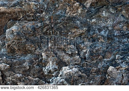 Dark Volcanic Rock Surface Texture With Colored Spots. Rock Formations Of Volcanic Rock Or Vulcanite