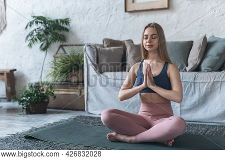 Full Length Of Mindful Young Woman In Sportswear Holding Hands In Praying Gesture While Sitting In L
