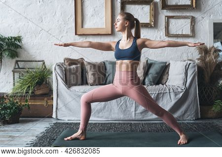Indoor Shot Of Young Sporty Woman Practicing Yoga Alone At Home, Standing In Warrior Two Pose In Liv