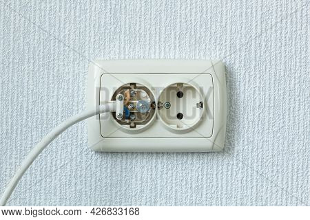 Household Electrical Outlet With A Broken Electrical Plug Inside. Bare Live Wires Sticking Out Of Th