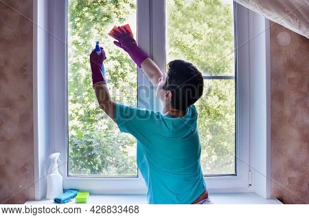 Woman With Short Black Hair In Rubber Gloves Washes Window In Her Apartment With Rag While Holding W
