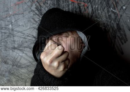 A Studio Portrait Of A Man In Hood Threatening With A Fist