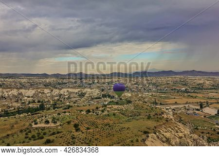 A Bright Hot Air Balloon Flies Over Cappadocia. At The Bottom Of The Valley, Gorges, Mountains. Dark