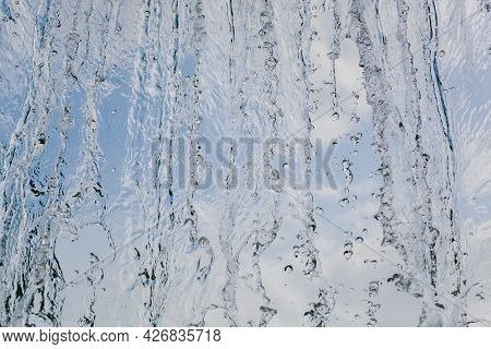 Inside View Of The Falling Water Of The Waterfall Against The Blue Sky. Beautiful Texture Of Frozen
