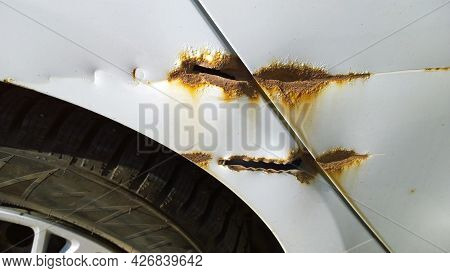 Sheet Metal Corrosion Above Tyre Wheel Of Old White Car Body. Rusty Messy Surface. Damaged Grunge Di