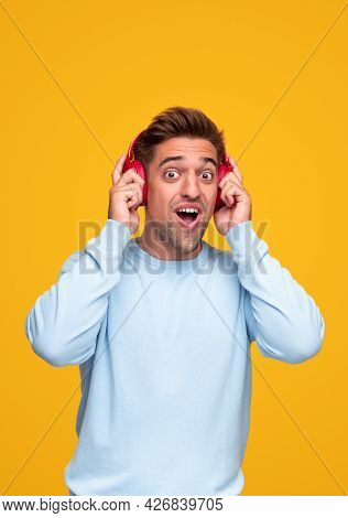 Shocked Young Man In Blue Sweatshirt Adjusting Headphones And Looking At Camera With Opened Mouth Wh