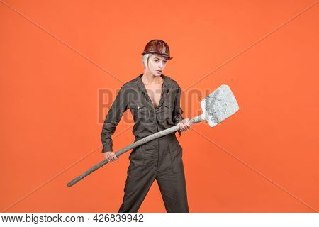 Woman Hard Worker In Protective Helmet And Boilersuit Hold Shovel On Orange Background, Labour Day