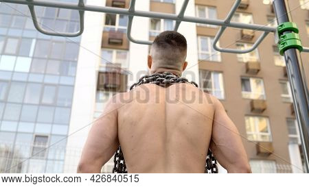 The Guy Walks On The Playground With A Chain Around His Neck. An Athlete Stands In A Gym With A Larg