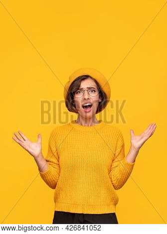 Astonished Young Female In Trendy Sweater And Beret Gesticulating And Looking At Camera With Opened
