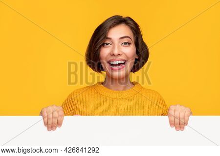Optimistic Young Woman In Knitted Sweater Smiling And Looking At Camera While Demonstrating Empty Po