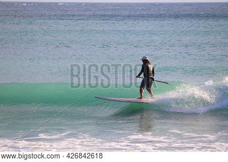 Kenting, Taiwan - November 28, 2018: Paddleboard Surfer Rides The Waves In Kenting Beach, Taiwan. Ke