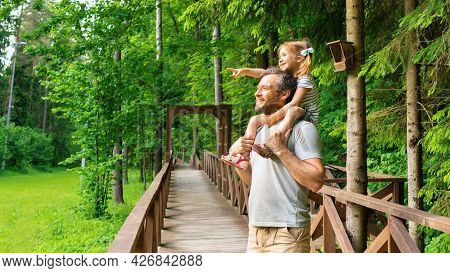 The Father Carries His Daughter On His Shoulders While Walking Along The Hiking Trail In The Reserve
