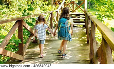 Children's Tourism Concept. Kids With Backpacks Go Hiking In The Reserve. The Two Sisters Head To Th