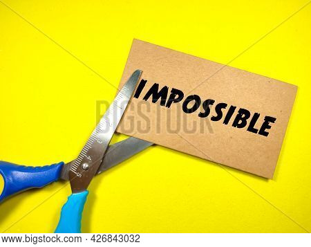 Business Concept.text Impossible On Brown Card With Scissors On Yellow Background.