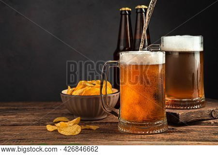 Pouring Chilled Beer Into Beer Mugs On A Dark Brown Background. Side View, Space For Copying. Oktobe