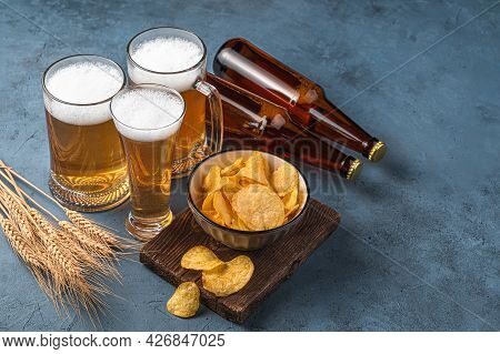 Beer, Chips And Wheat Spikelets On A Dark Blue Background. Side View, Space For Copying.