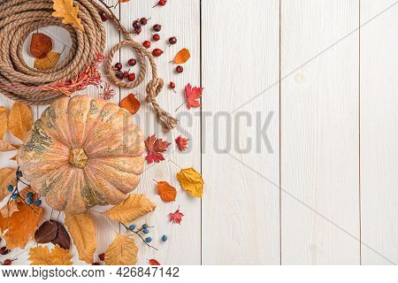 Festive Autumn Decor Made Of Pumpkin And Autumn Leaves On A Light Wooden Background. Top View, Copy
