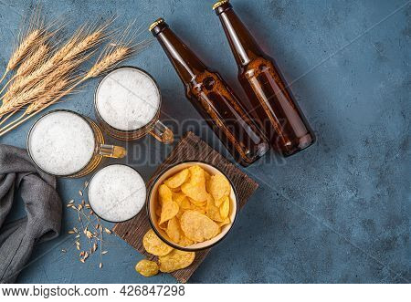 Beer, Chips And Wheat Spikelets On A Dark Blue Background. Top View.
