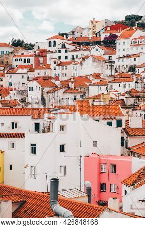 A Vertical Shot Of The Hill Fulfilled With Typical Antique Colorful Portuguese Houses With Triangle