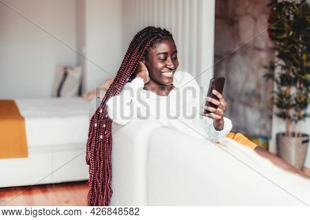 A Portrait Of A Young Cheerful Black Female With Braided Hair Having A Phone Video Call Or A Vloggin