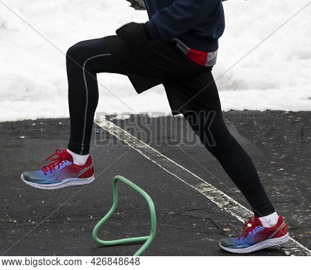 High School Runner Working Out Steppoing Over Mini Hurdles In A Parking Lot With Snow In The Backgro