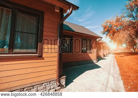 Wide-angle Shot Of A Group Of Similar Wooden Houses Of A Youth Hostel Or A Campsite Stretching Into