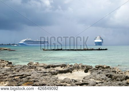The View Of Two Cruise Ships Drifting Near George Town On Grand Cayman Island And The Remains Of A S