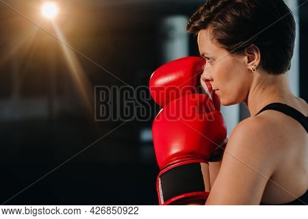 Portrait Of A Female Boxer In Red Gloves In The Gym During Training