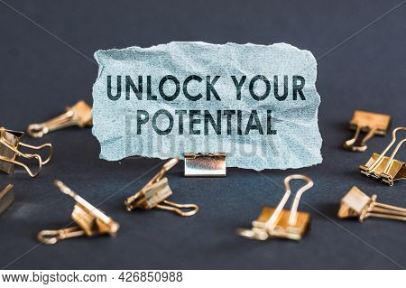A Scrap Of Blue Paper With Clips On A Gray Background With The Text - Unlock Your Potential.