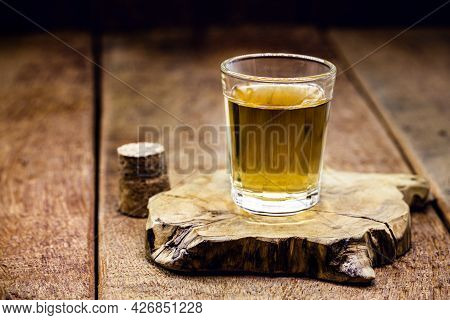 Glass Of Distilled Alcoholic Beverage On Wooden Background With Copy Space For Text. Call For Rum Or