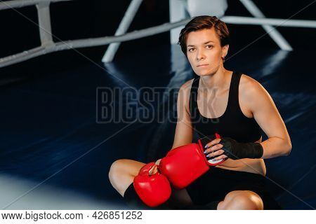 Portrait Of A Female Boxer In Red Gloves In The Gym After Training