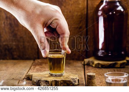 Male Hand Holding A Glass Of Distilled Alcoholic Beverage, Called