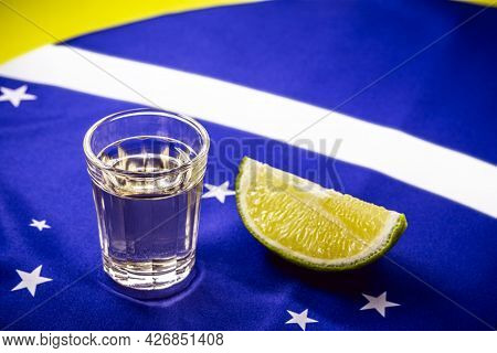 Glass Of Distilled Beverage Made From Sugar Cane, Over The Brazilian Flag, Concept Of The National P