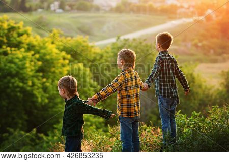 Group Of Happy Children Playing On Meadow, Sunset, Summertime. Three Brothers Holding Hands On Hill