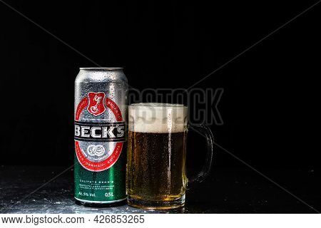 Can Of Beck`s Or Becks Beer And Beer Glass On Dark Background. Illustrative Editorial Photo Shot In