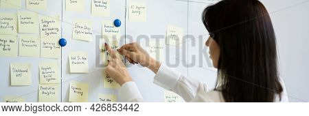 Woman Writing On Sticky Notes On Kanban Project Board