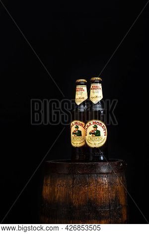 Bottle Of Birra Moretti Beer On Wooden Barrel With Dark Background. Illustrative Editorial Photo Buc