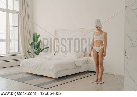 Full Length Of Healthy Young Slender Woman In Underwear With Bath Towel Wrapped On Head After Mornin